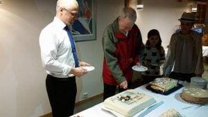 Første leder i laget, Egil Ruud Røhne og nåværende Arnljot Teigland åpner jubileumskaka